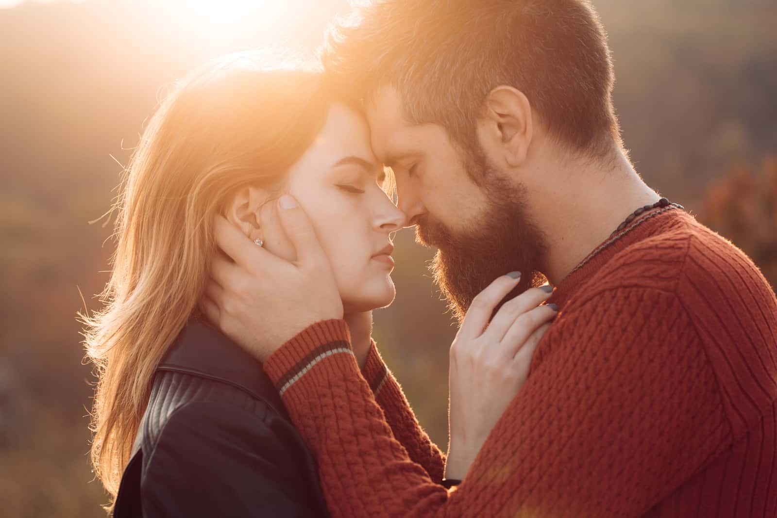 Mannen med skägg håller kvinnans huvud med ömhet