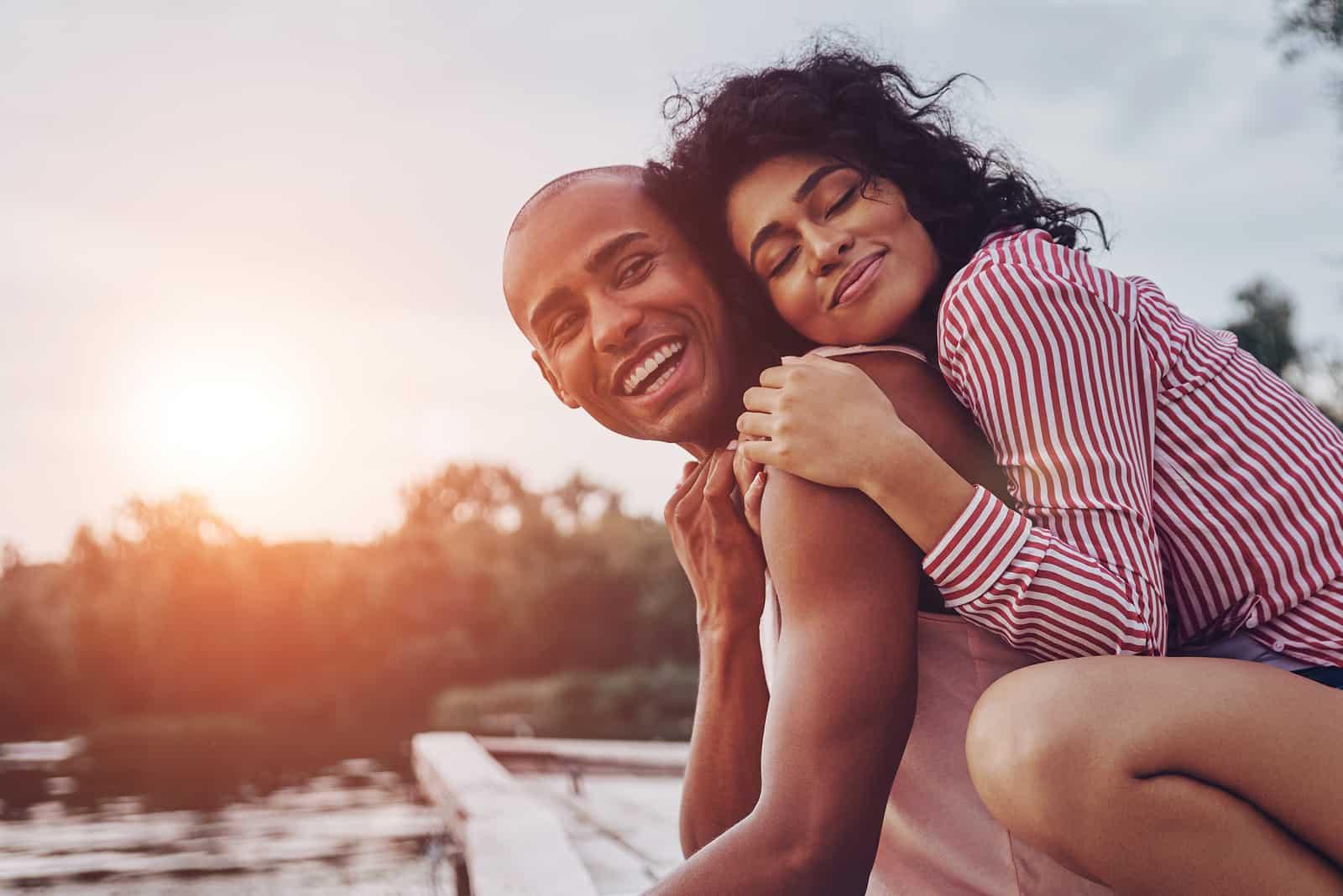 ungt par som omfamnar och ler