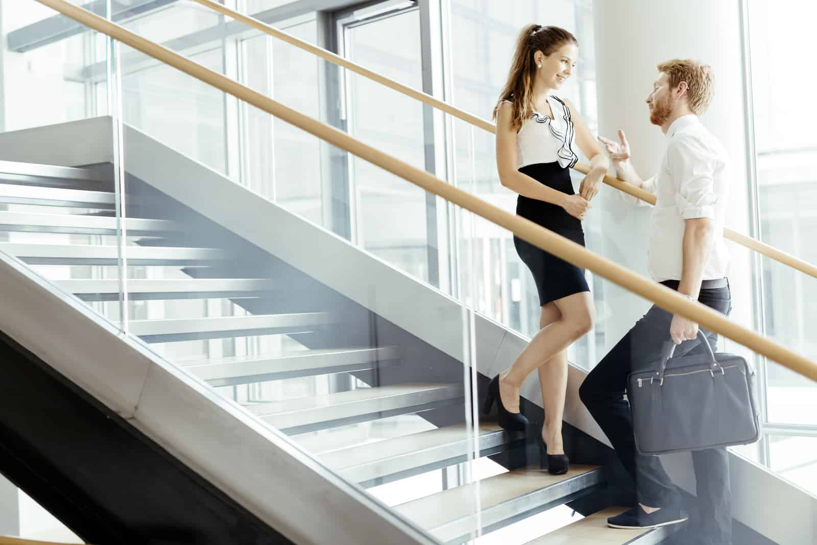 Affärskollegor som talar i trappor och flörtar