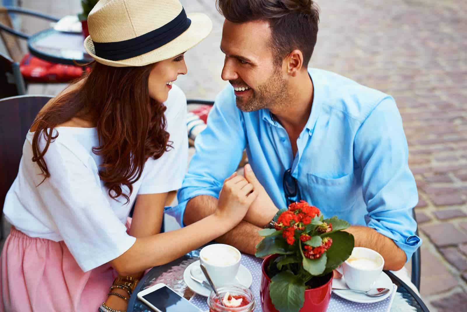 Par som är förälskade att sitta i kafé som ser varandra