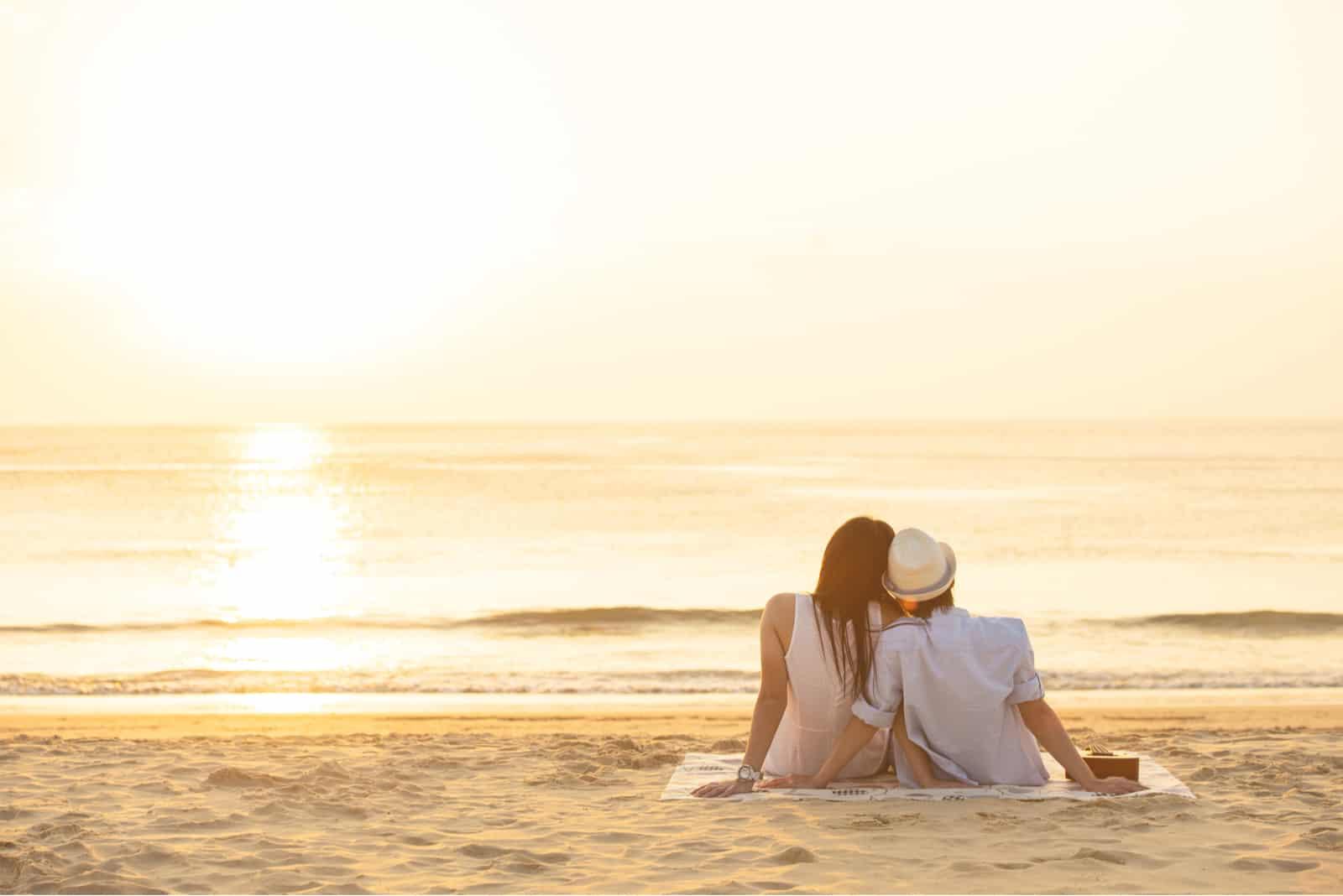 Par som förälskat håller ögonen på solnedgången tillsammans på stranden