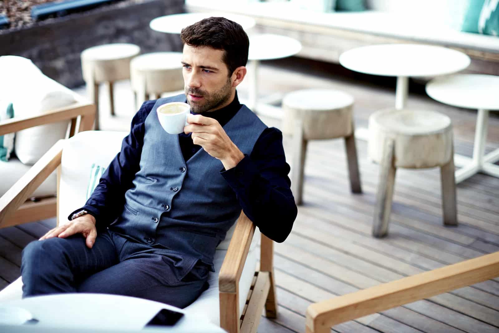 Säker affärsman i dräkt som tycker om en kopp kaffe