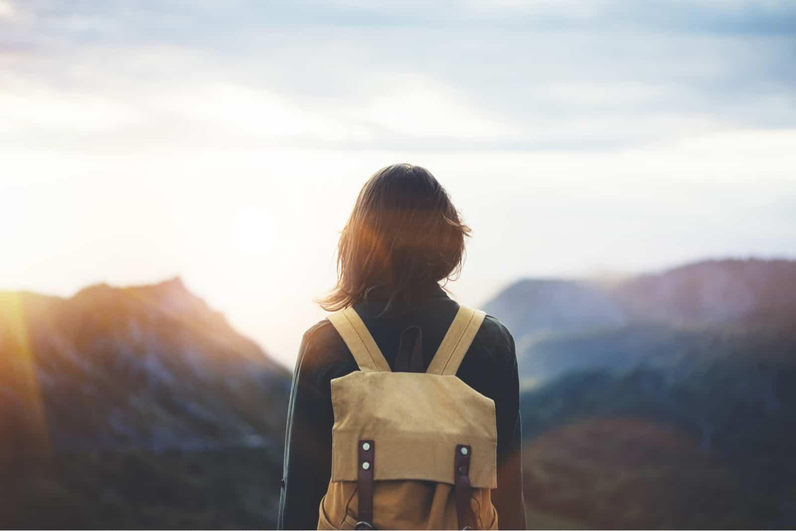Ung flicka för hipster med den ljusa ryggsäcken som tycker om solnedgång på maximum av dimmigt berg