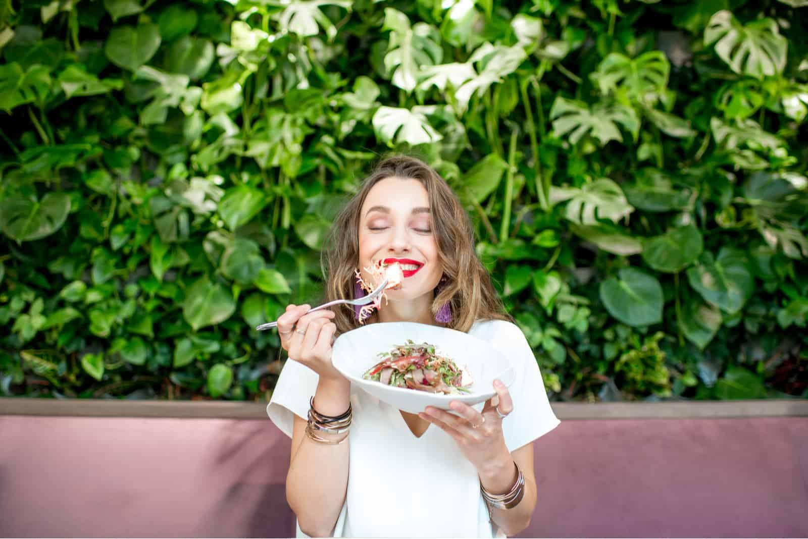 Ung och härlig kvinna som tycker om sund sallad