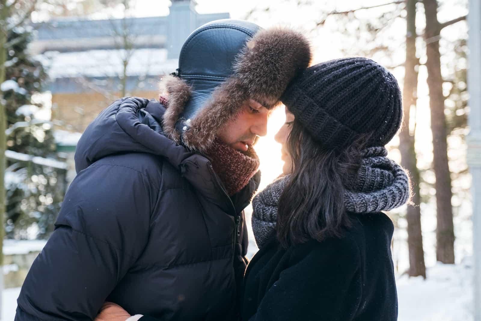 Unga sinnliga par som är förälskade som utomhus omfamnar i vinterdag