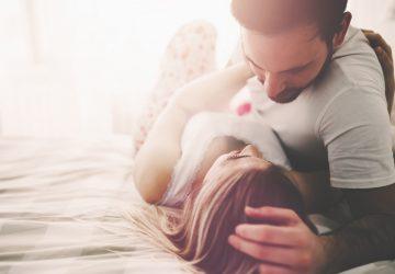 Par i kärlek som rymmer händer sover i sängen med solljus på morgonen