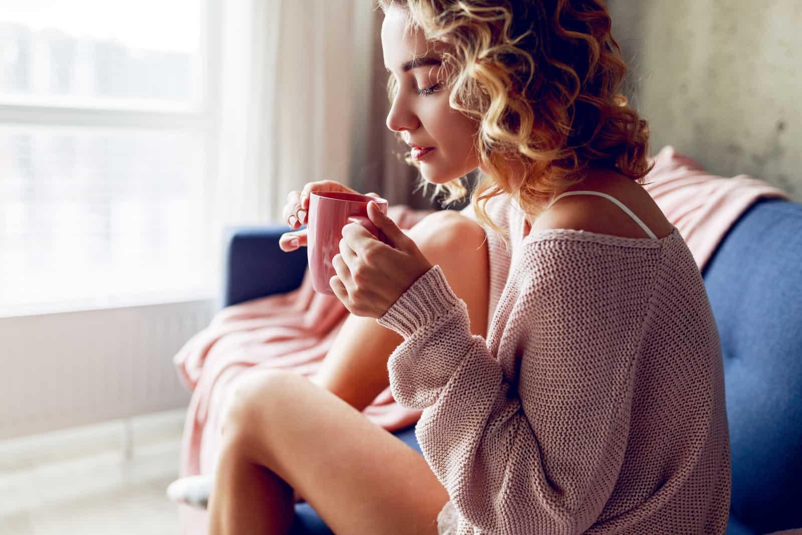 fundersam kvinna som dricker kaffe tidigt på morgonen