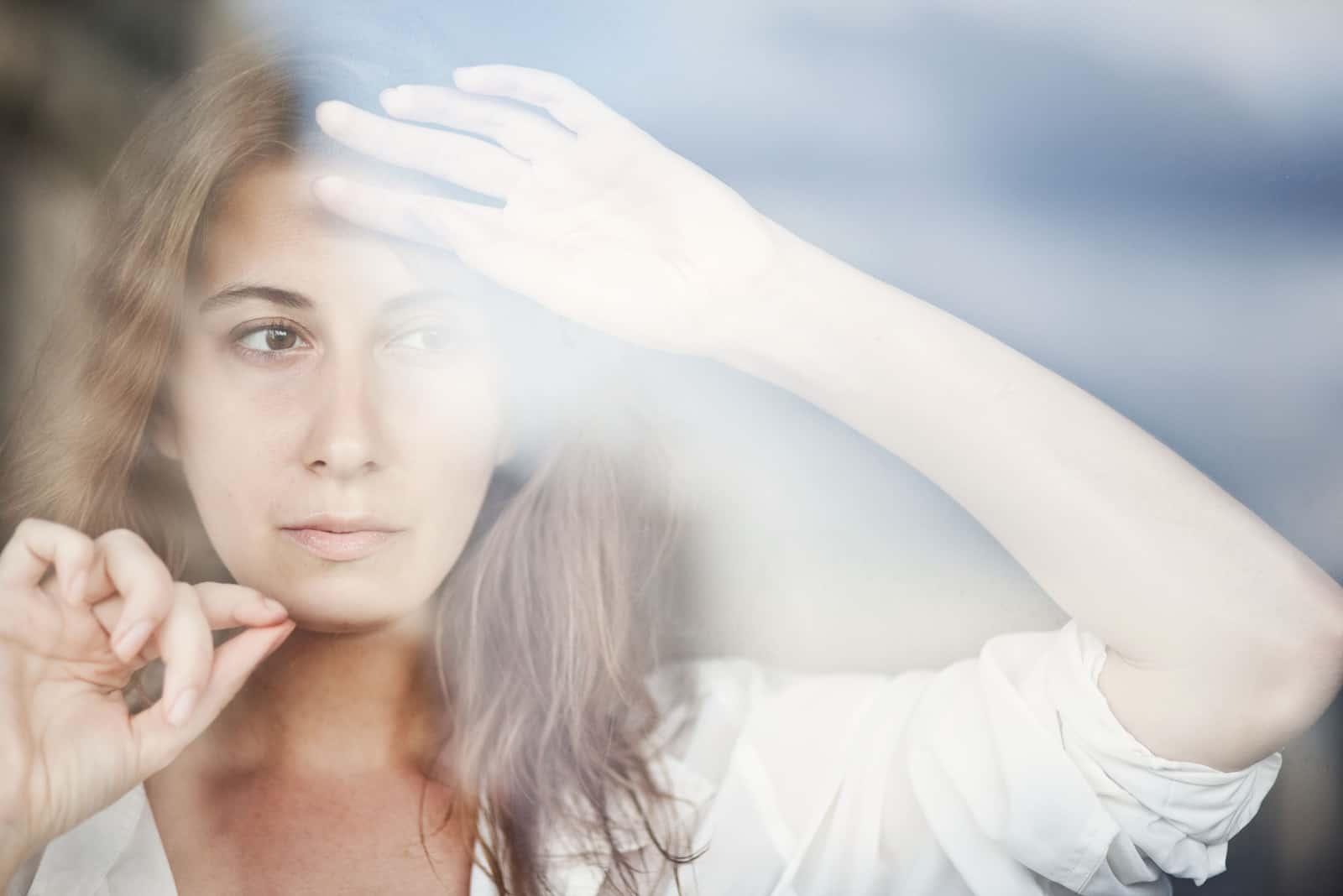 fundersam kvinna som tittar genom fönstret