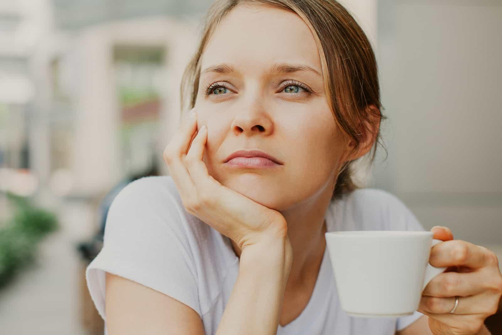 fundersam ung vacker kvinna som dricker kaffe