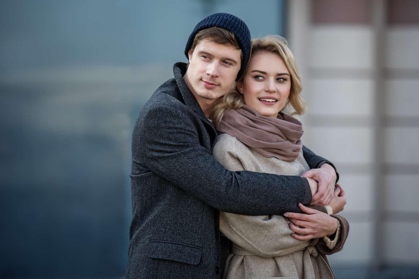 härligt attraktivt par som kramar varandra medan de tittar in på avstånd