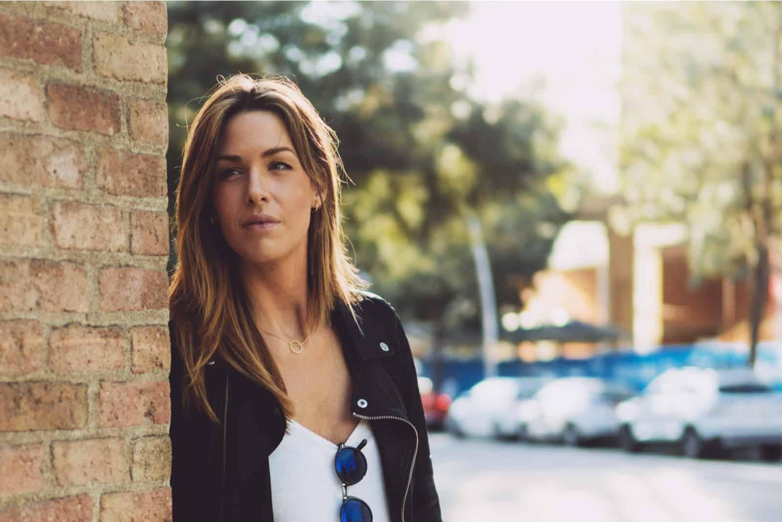 kvinna med långt hår som bär läderjacka som ser åt sidan