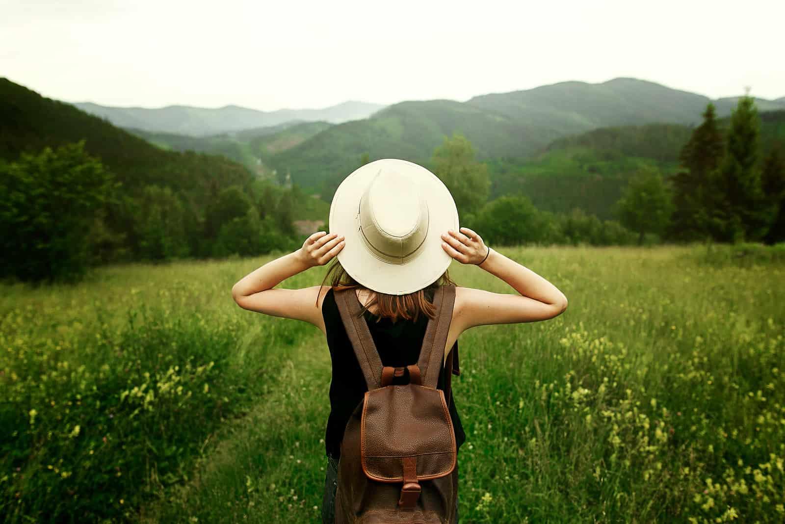 kvinna resenär med ryggsäck håller hatt och tittar på fantastiska berg och skog