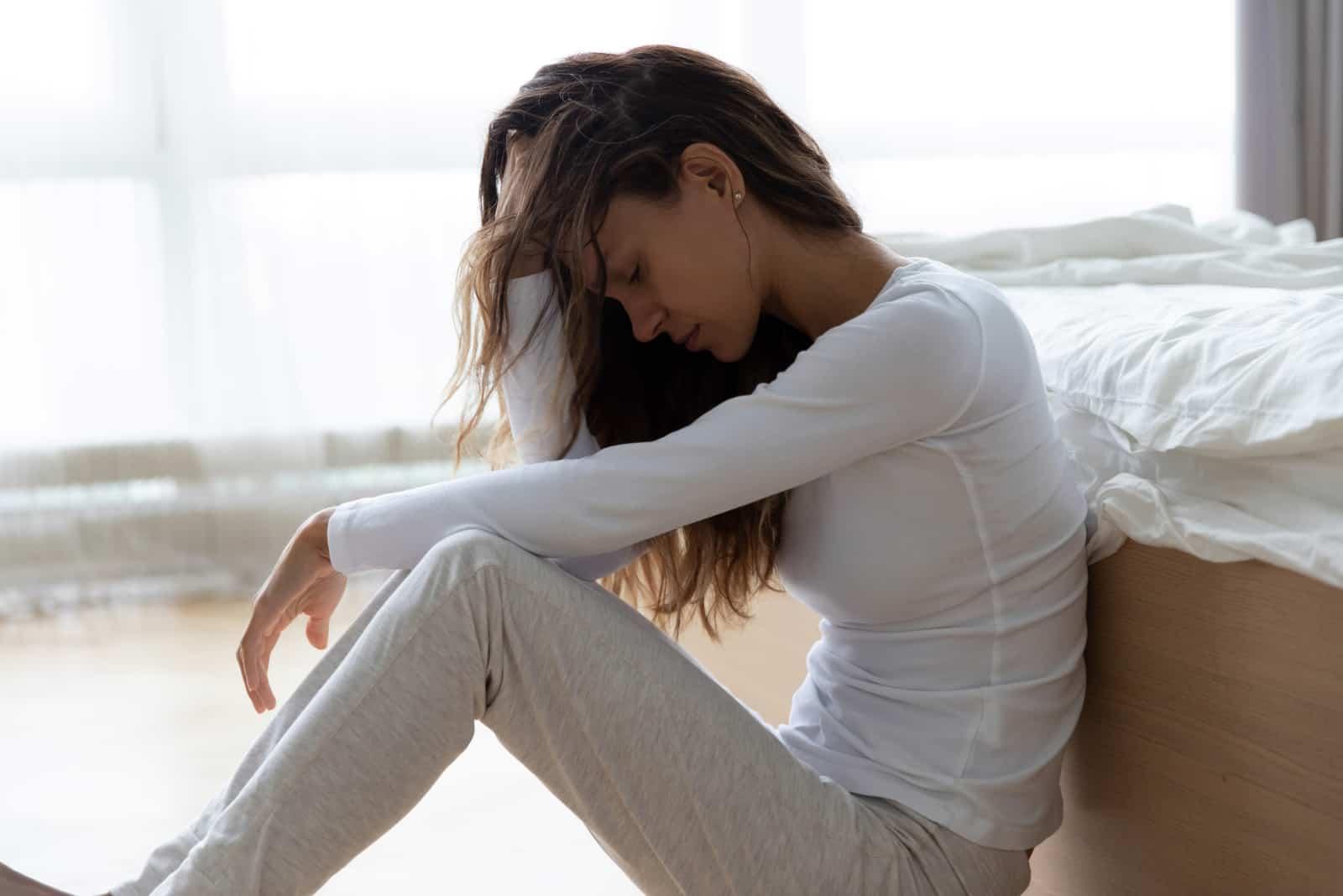 kvinna röra hår, sitter på golvet hemma