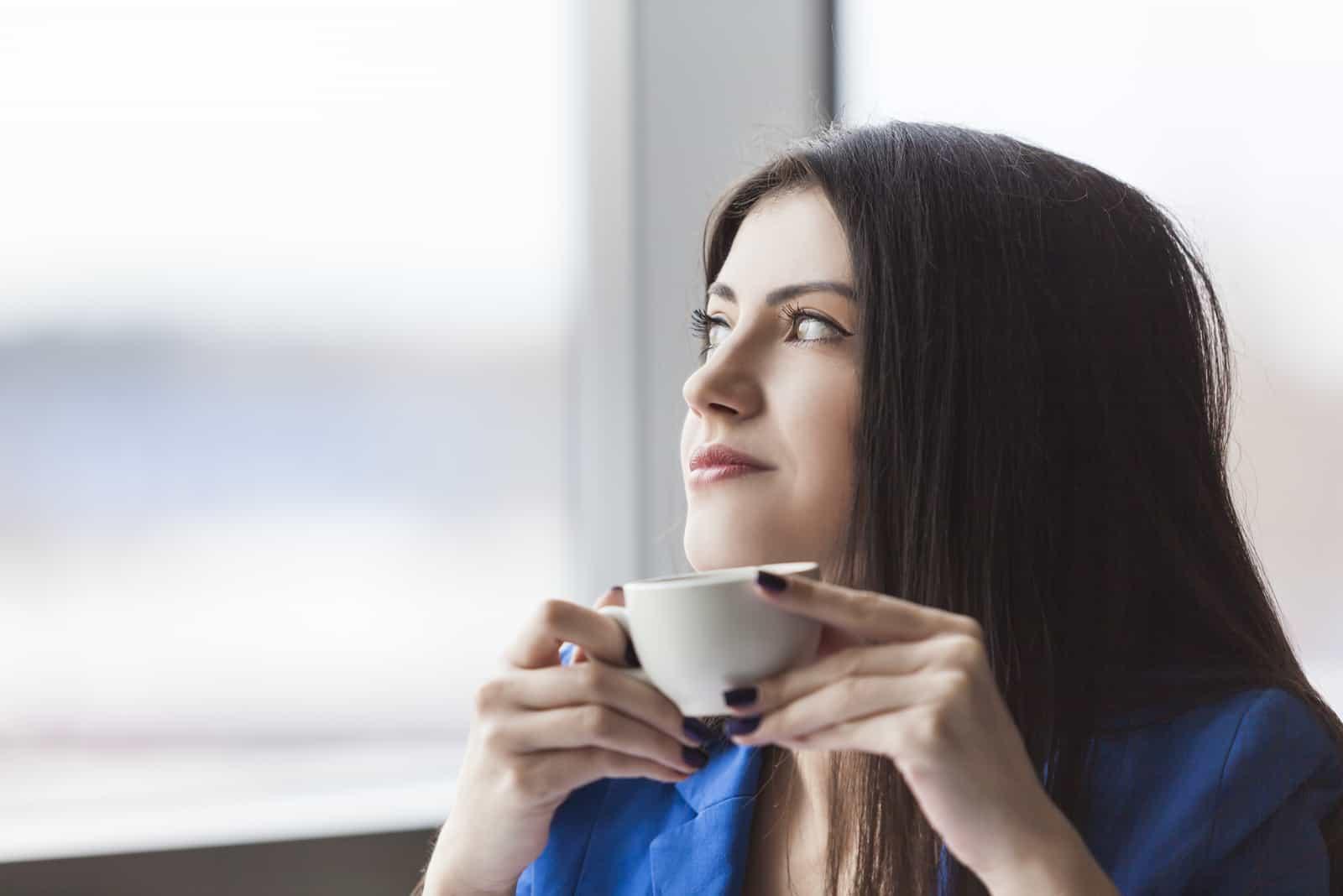 kvinna som håller en vit kaffekopp och tittar i kontorsfönstret (1)