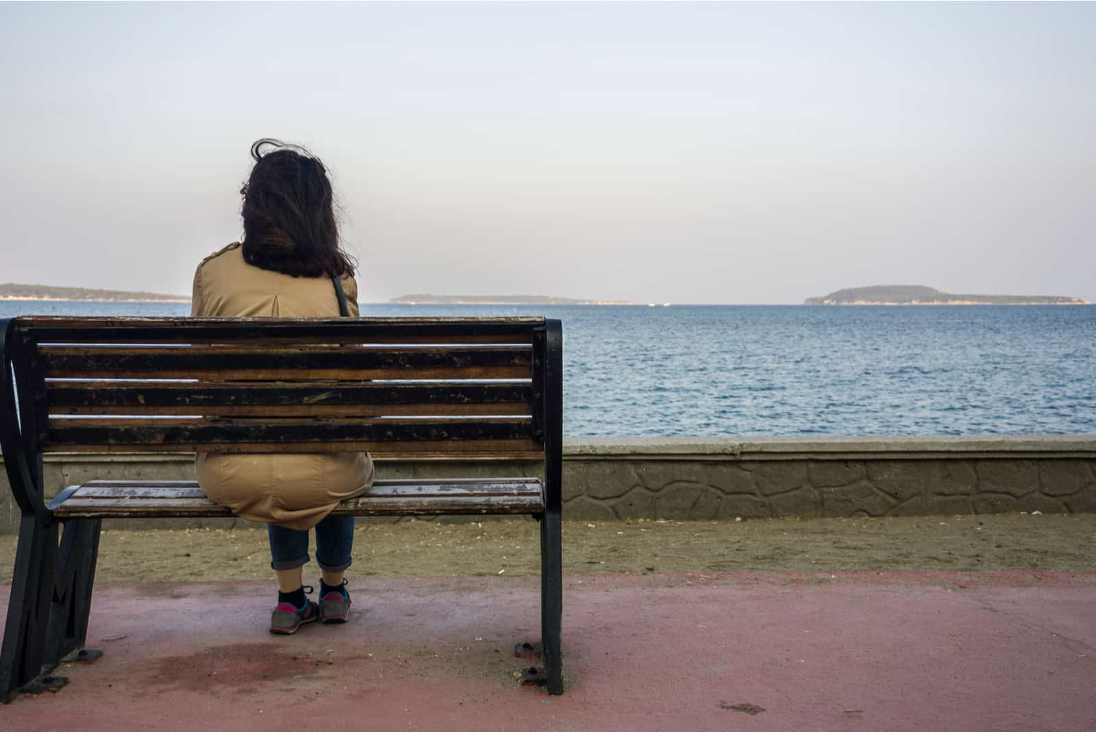 kvinna som sitter på bänken ensam