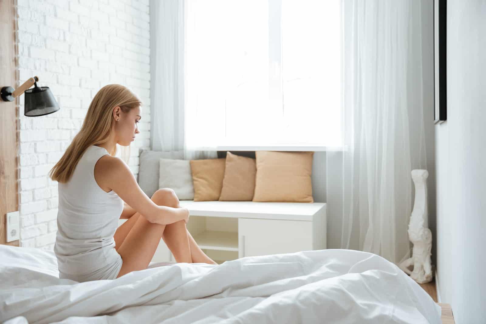 kvinna som sitter på sängen ensam