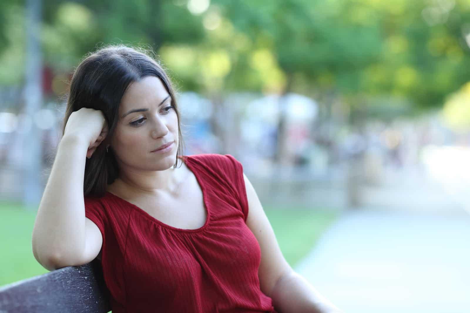 kvinnasammanträde på en bänk i en park som tittar bort