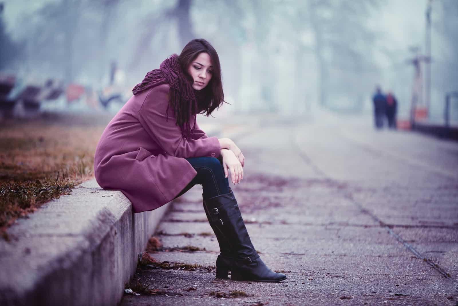 ledsen brunettkvinna som sitter ensam utomhus