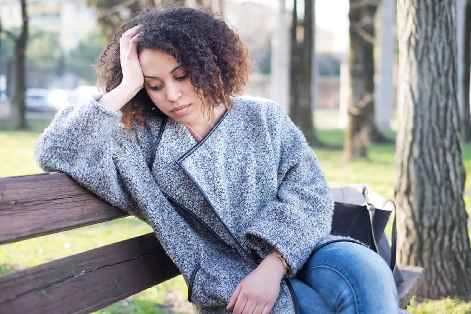 ledsen kvinna som sitter på bänken ensam