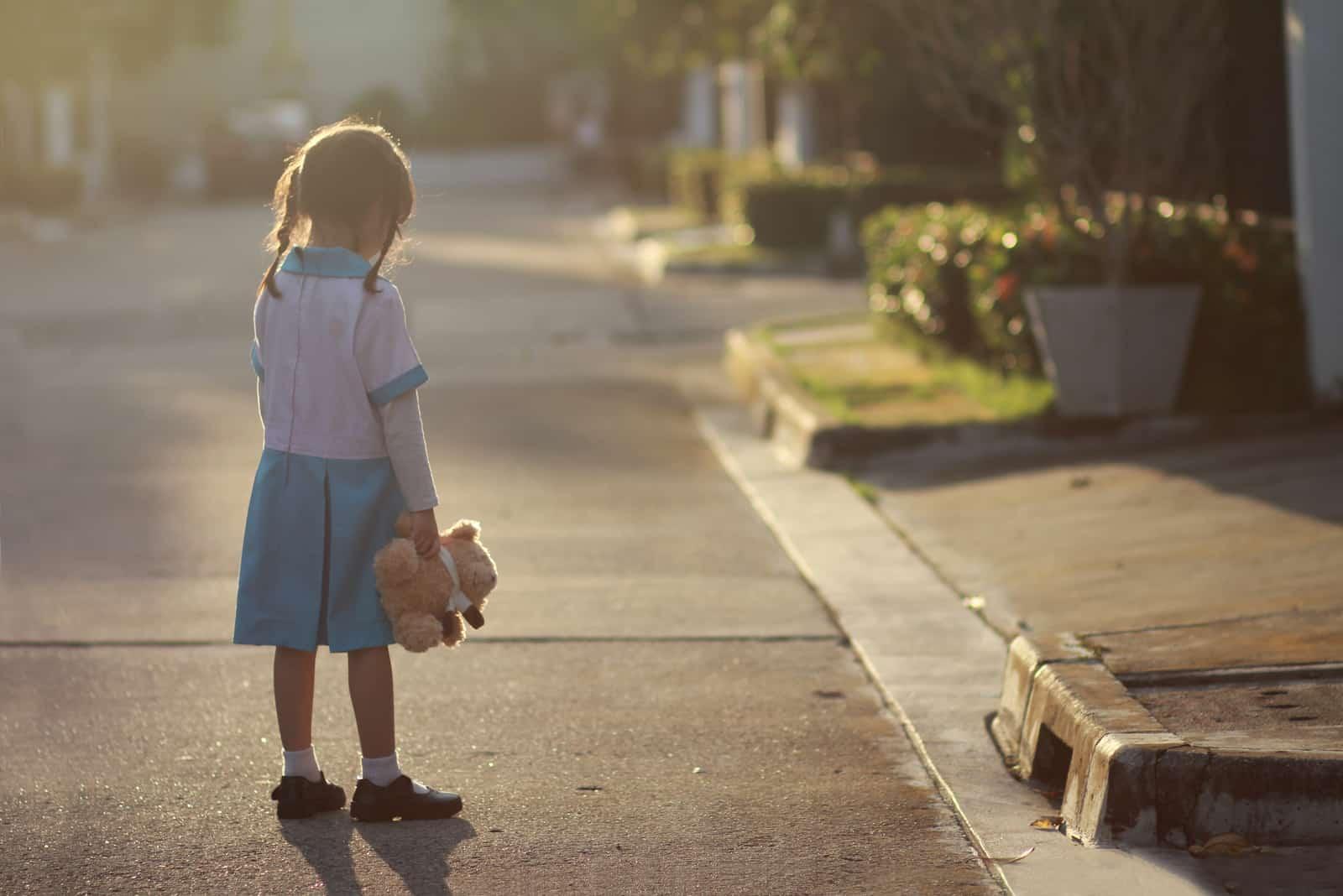 liten flicka stå ensam på gatan