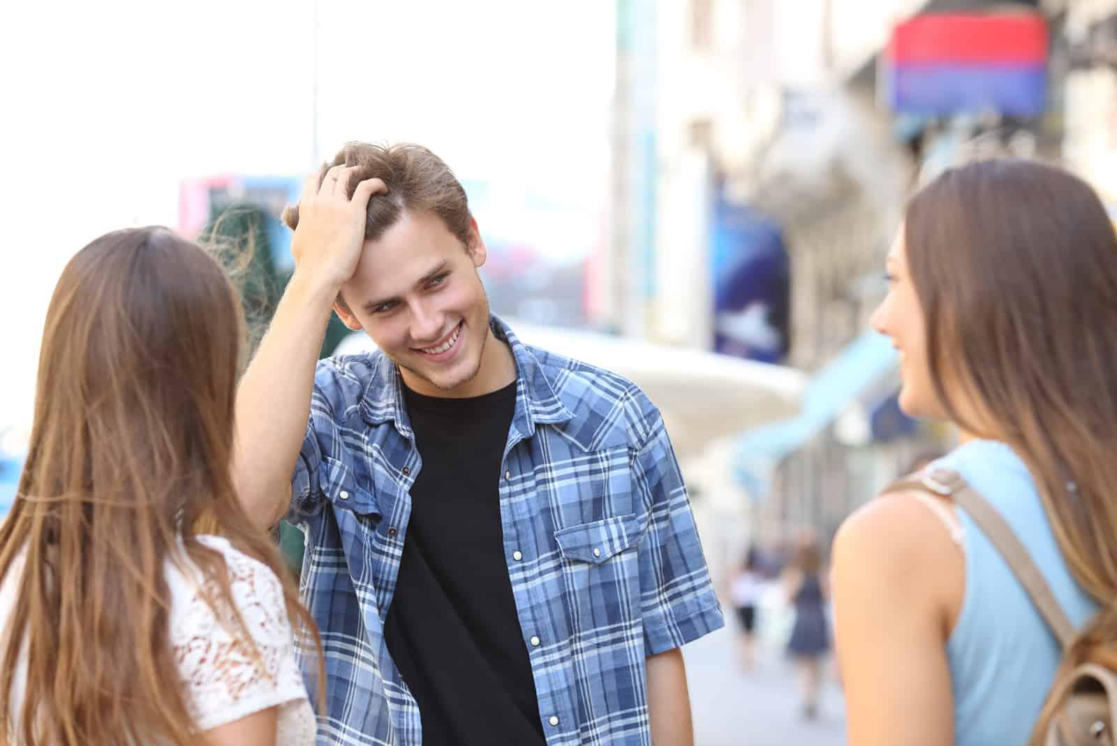 man flirta med två flickor på gatan