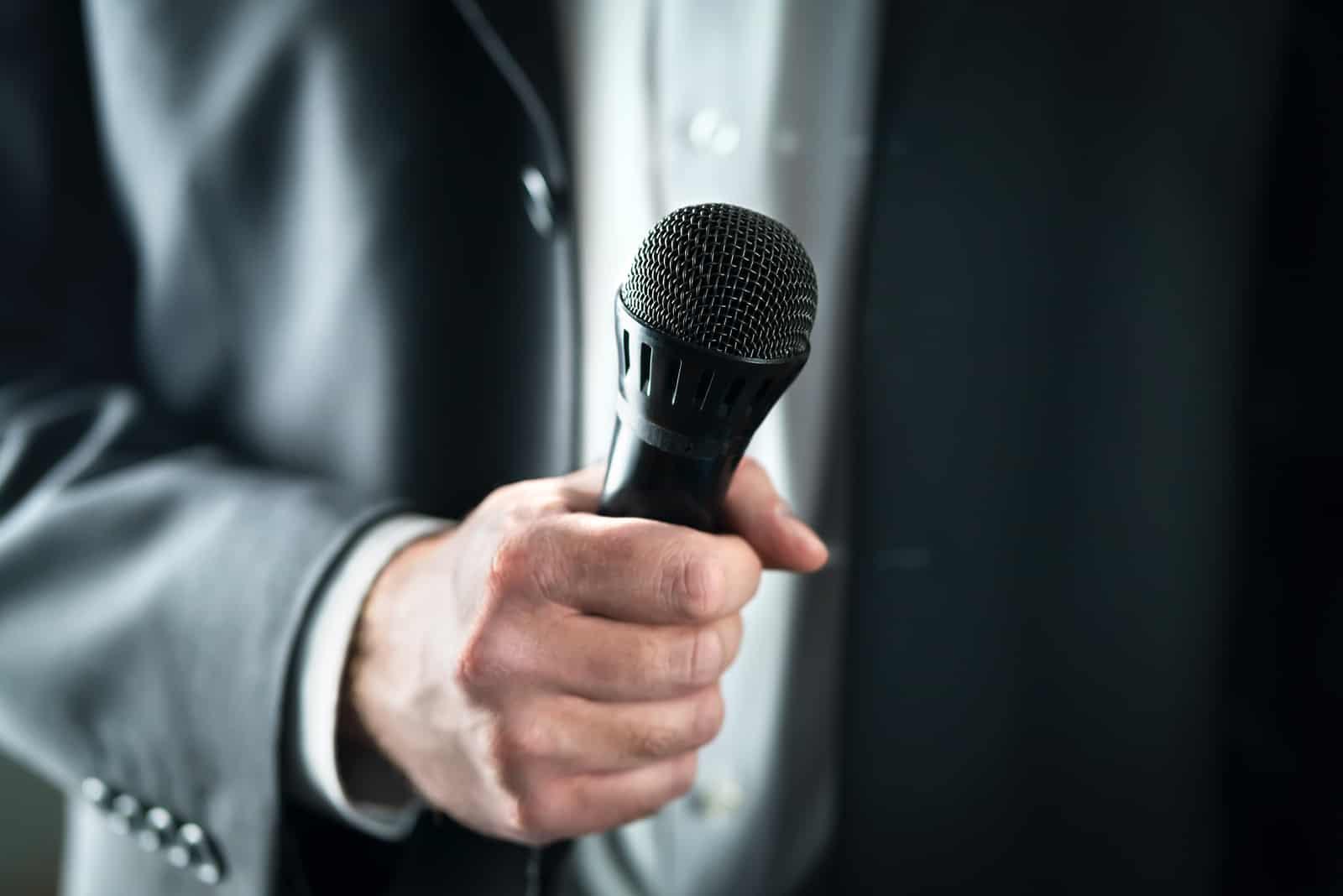 man håller mikrofon