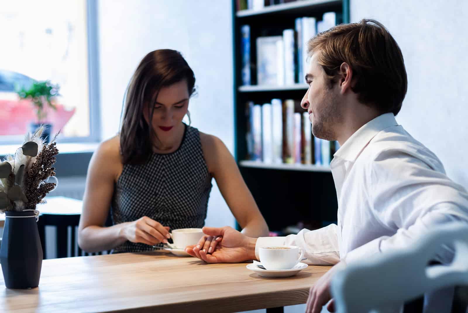 par på ett kafé vid ett bord dricker kaffe som ler mot varandra