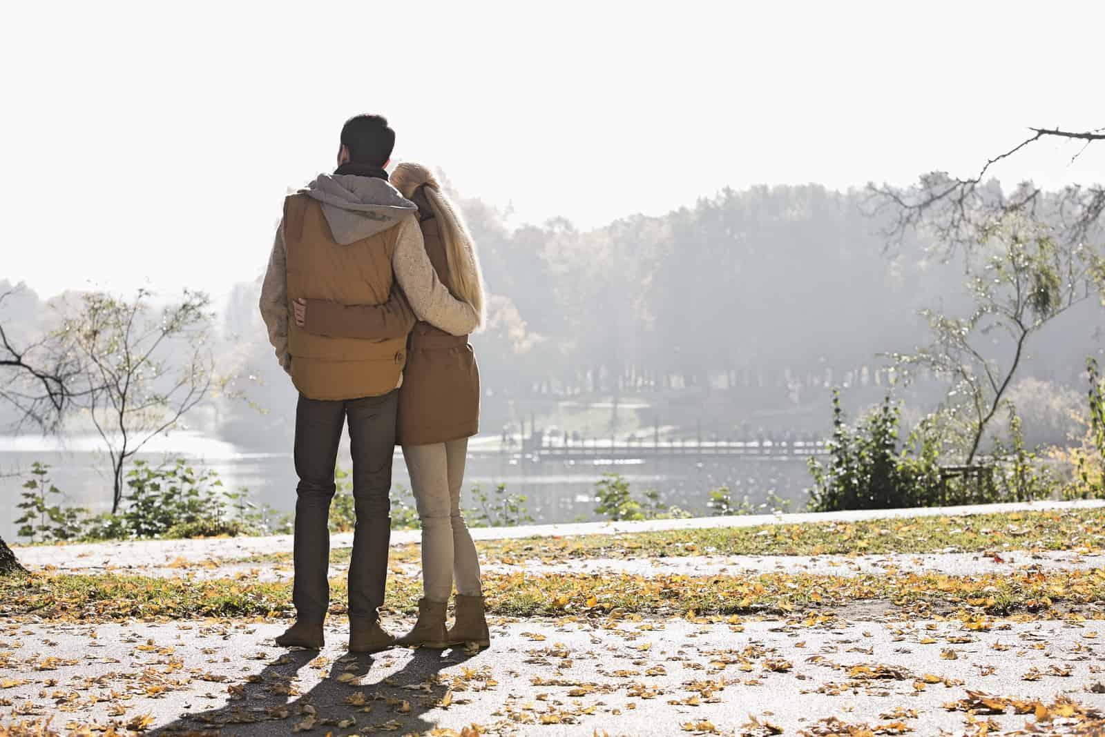 par som tittar på sjön i park