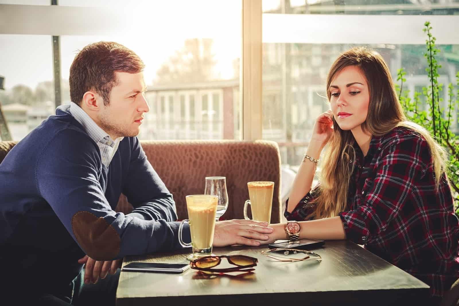 seriöst par som sitter vid bordet