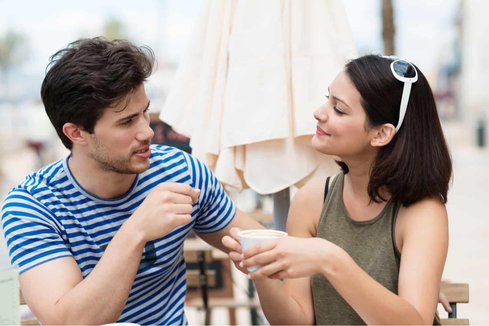 ungt par som dricker kaffe utomhus