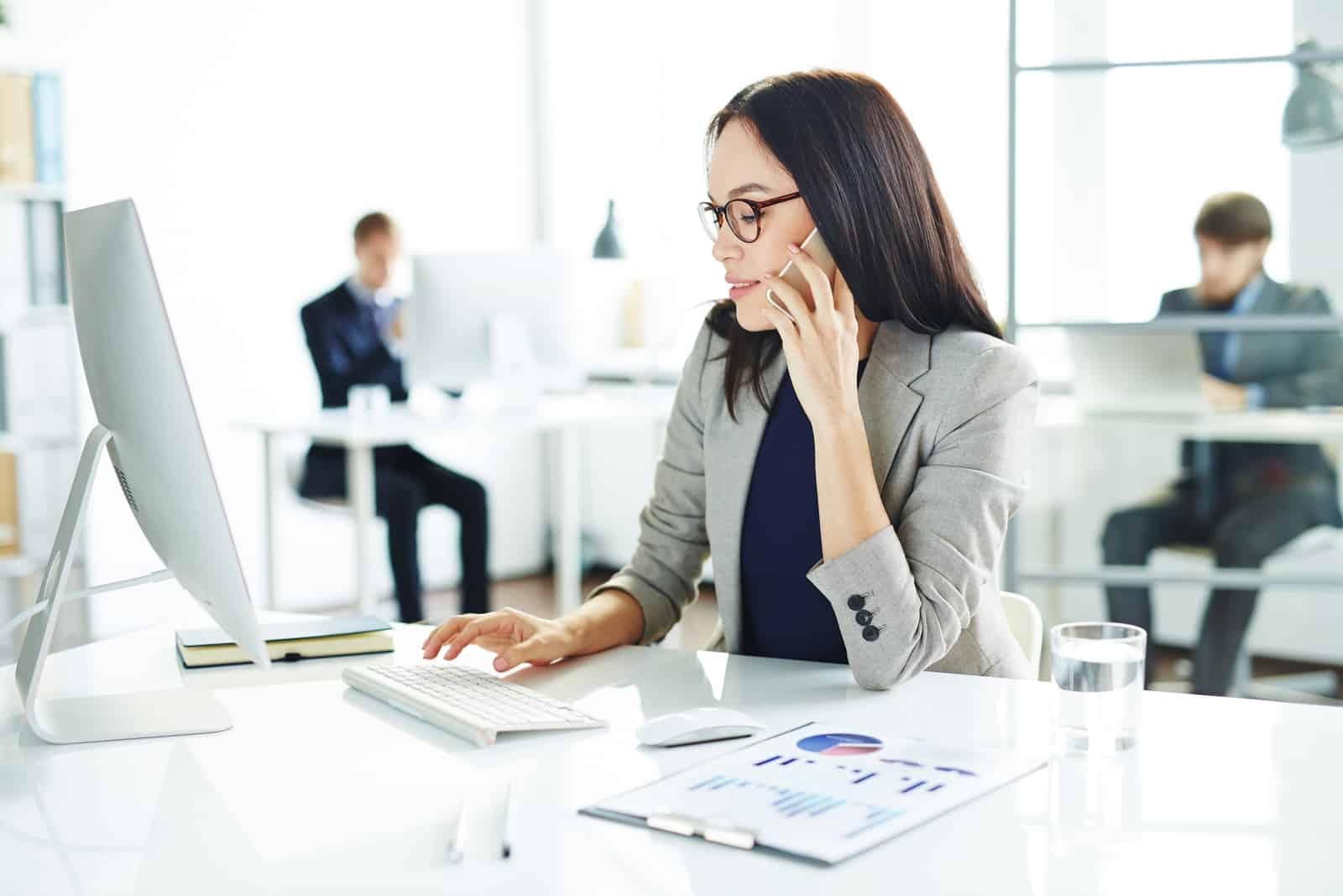 upptagen kvinna som sitter vid skrivbordet och pratar i sin telefon