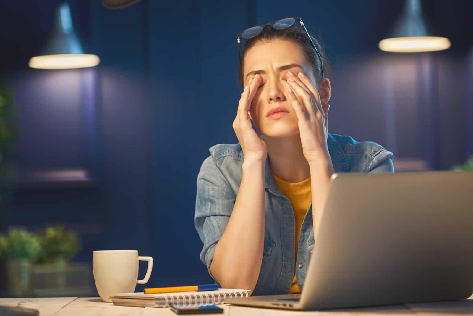 vacker kvinna som arbetar på en bärbar dator på natten hemma