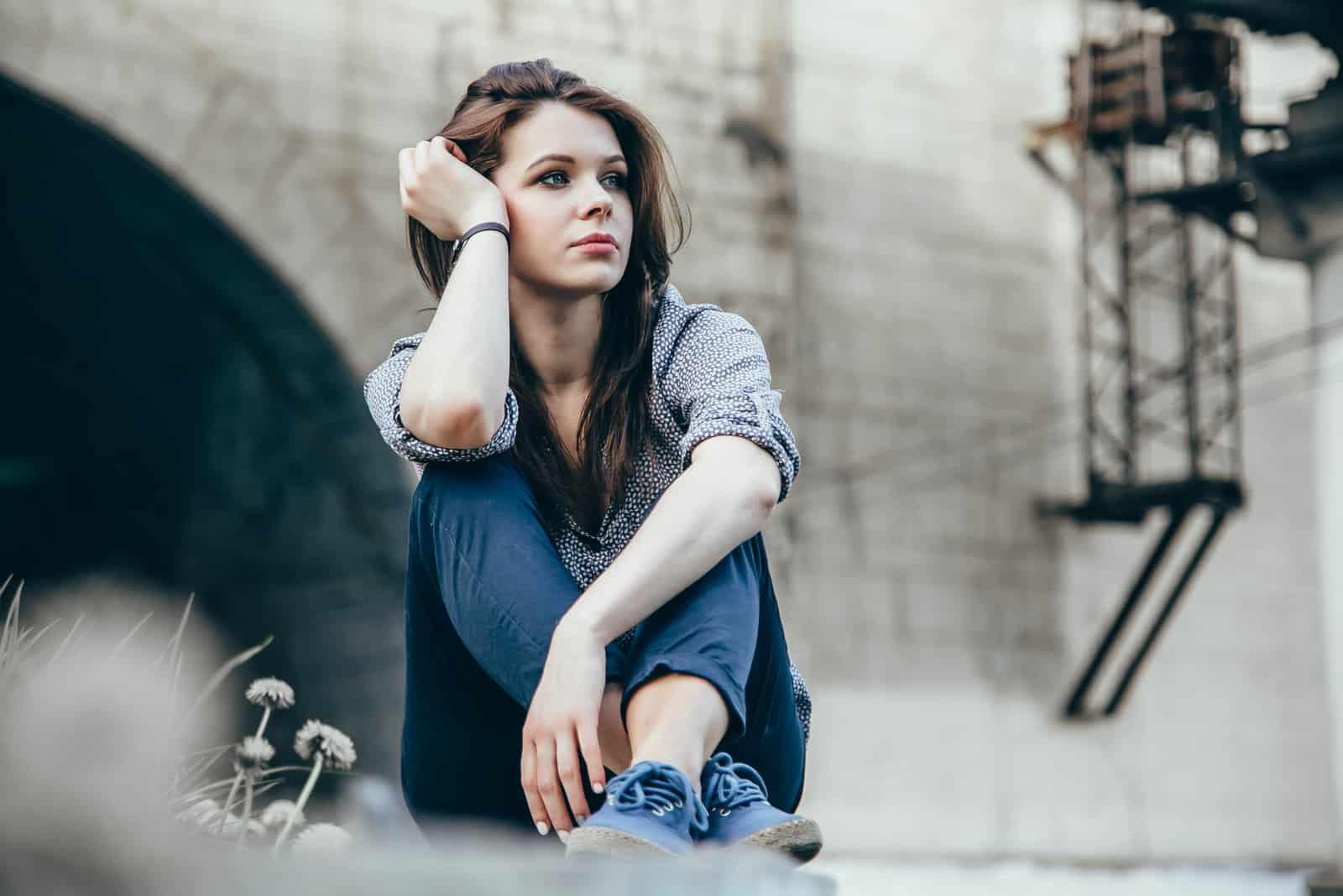 vacker sorglig tonårsflicka som sitter utomhus