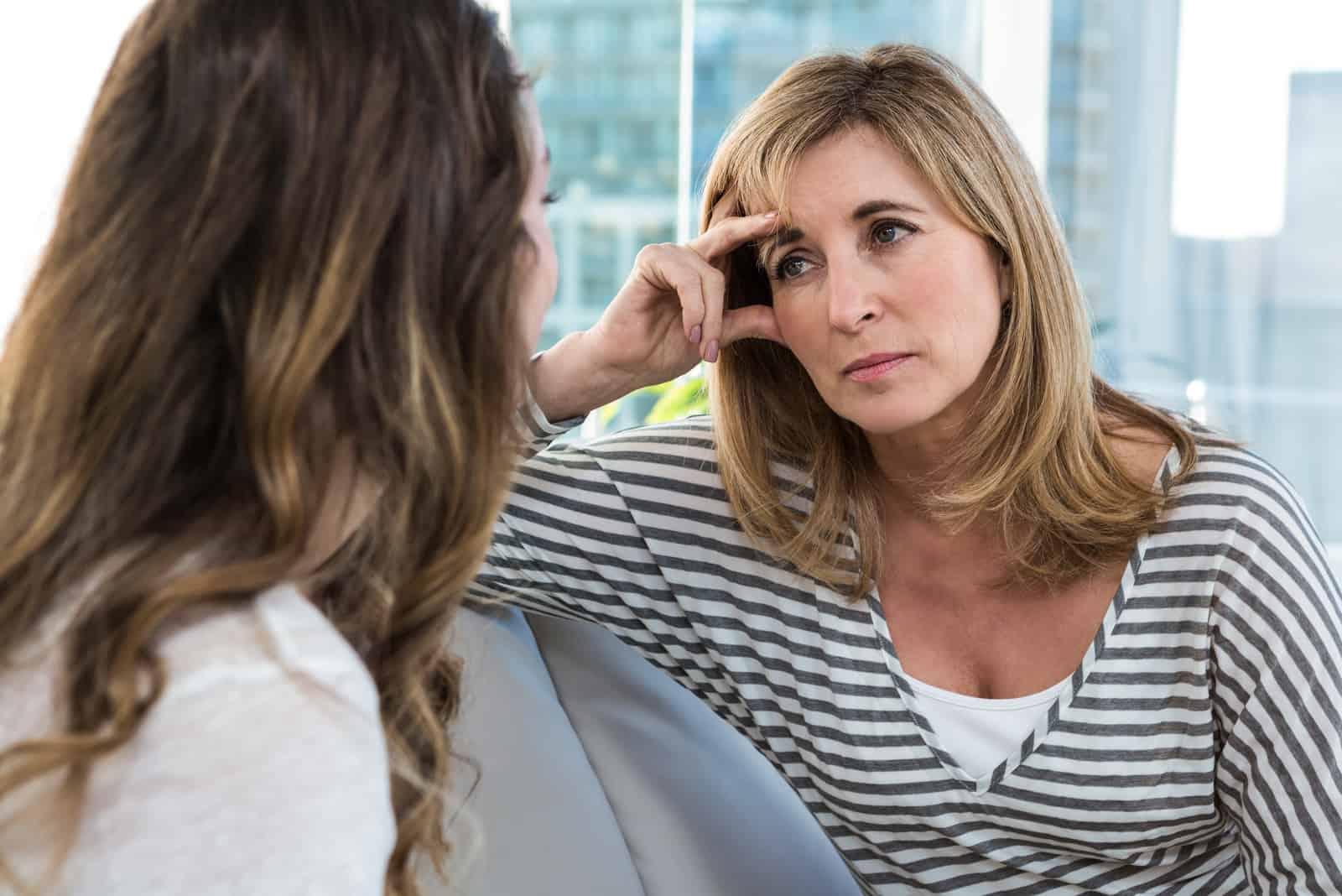 Bekymrad moder som talar till dottern på soffan
