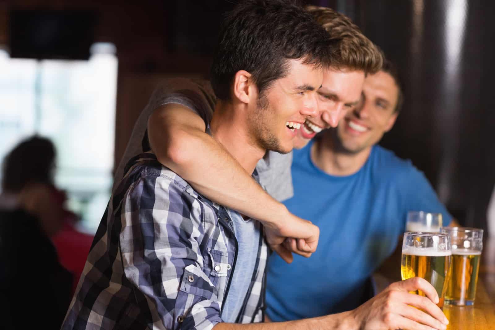 Lyckliga vänner som hamnar över pints i en bar