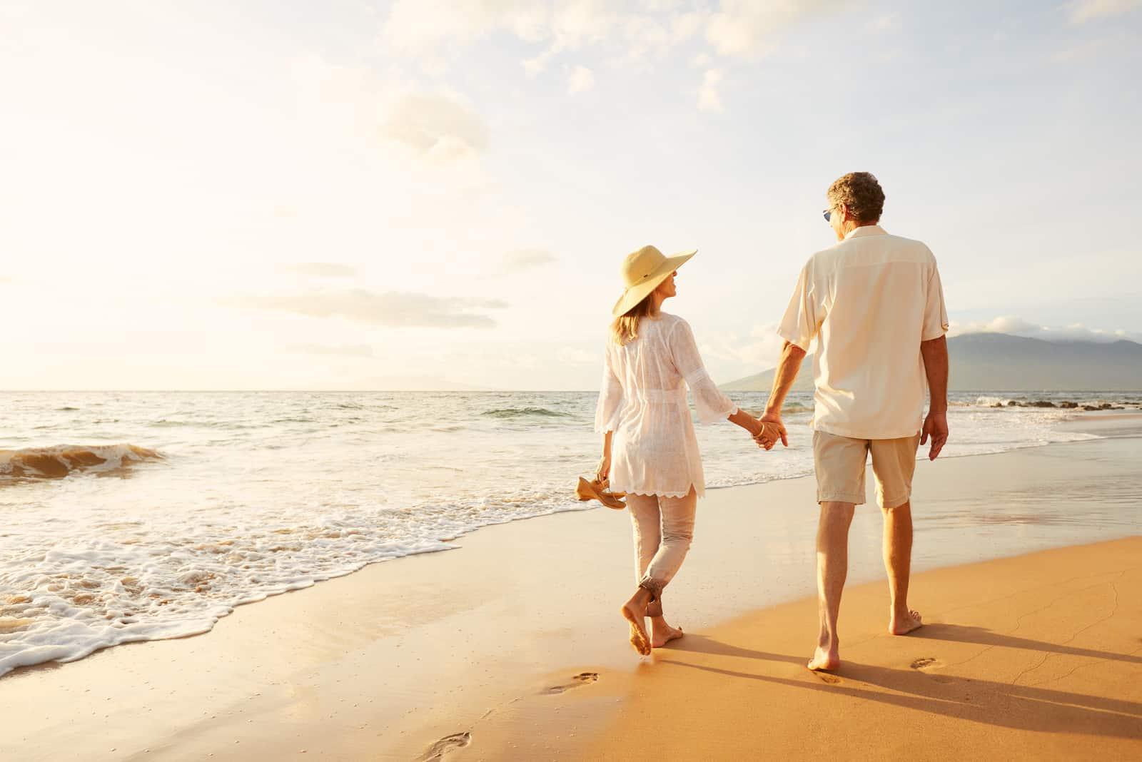 Par som tycker om härlig solnedgång, går på stranden