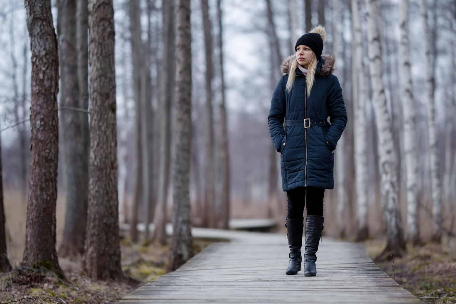 Ung kvinna i mörka varma kläder som långsamt går på träslinga