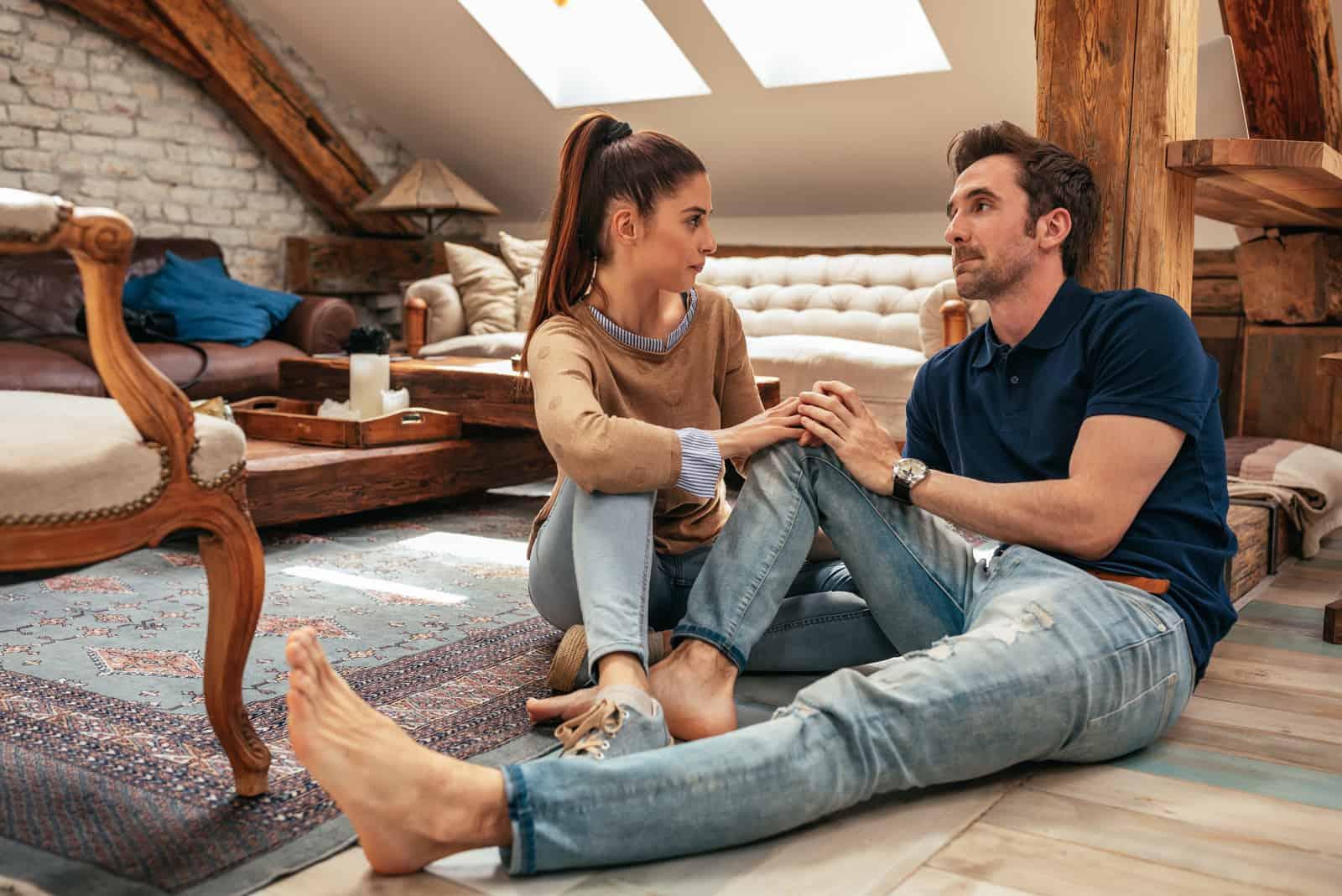 attraktivt ungt par som talar i vardagsrummet