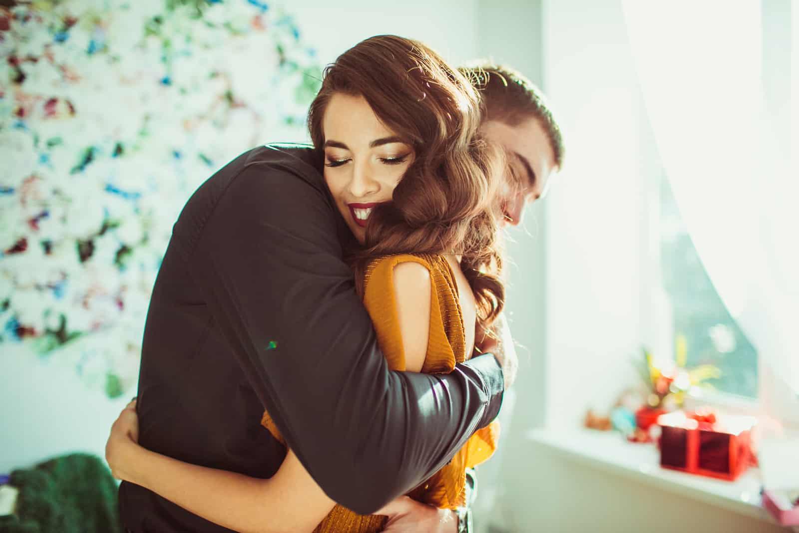 dam lutar sig mot mans axel medan han kramar henne
