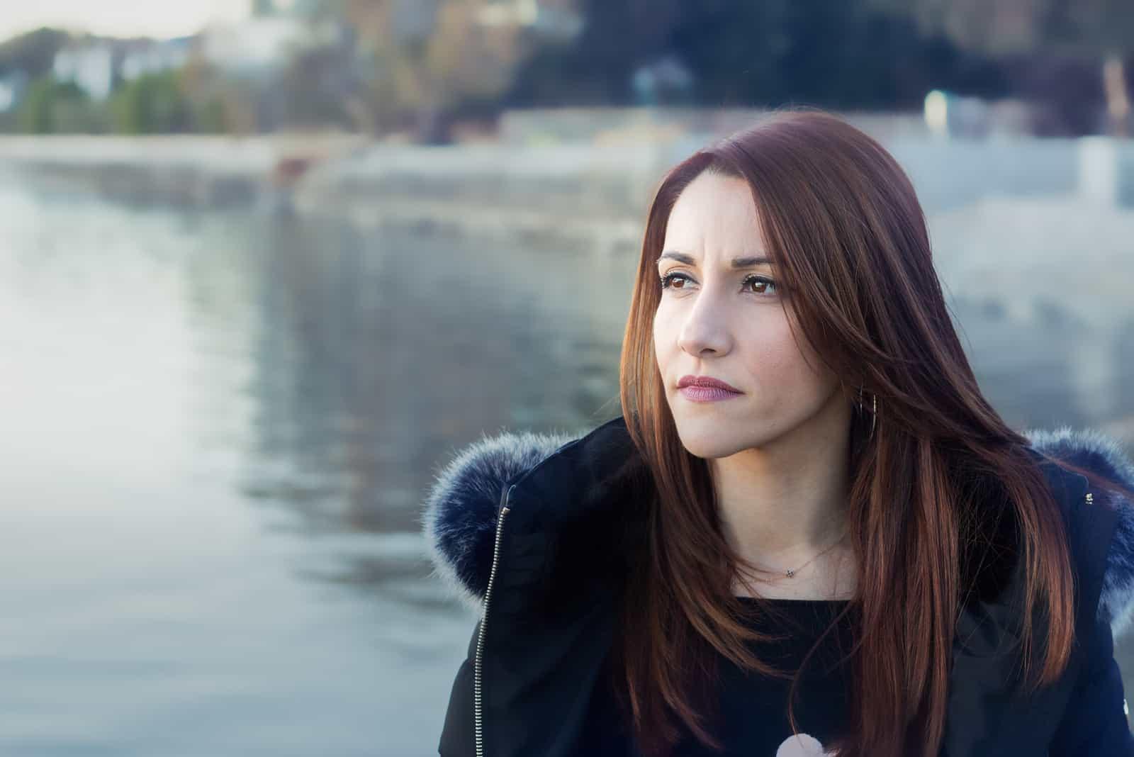 fundersam kvinna som står vid sjön ensam