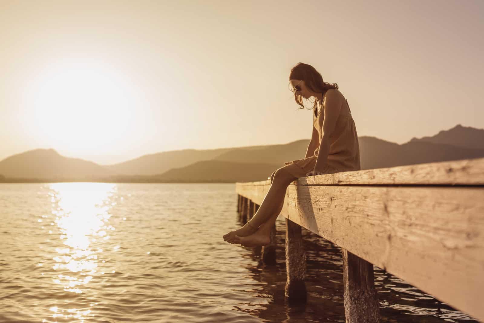 smuk ung kvinde sidder på en mole i en sø