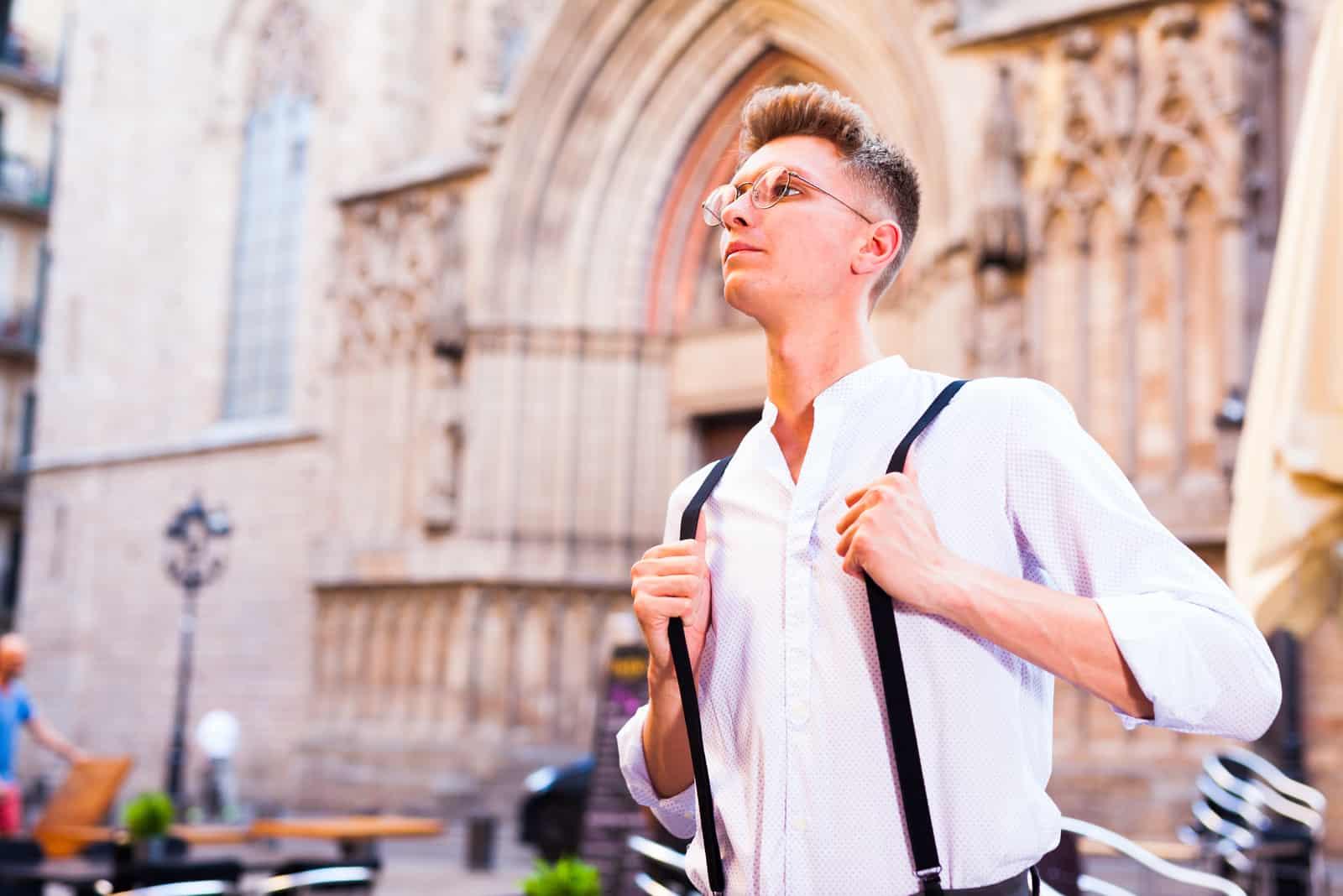 kille i skjorta och byxor med hängslen som går runt i staden