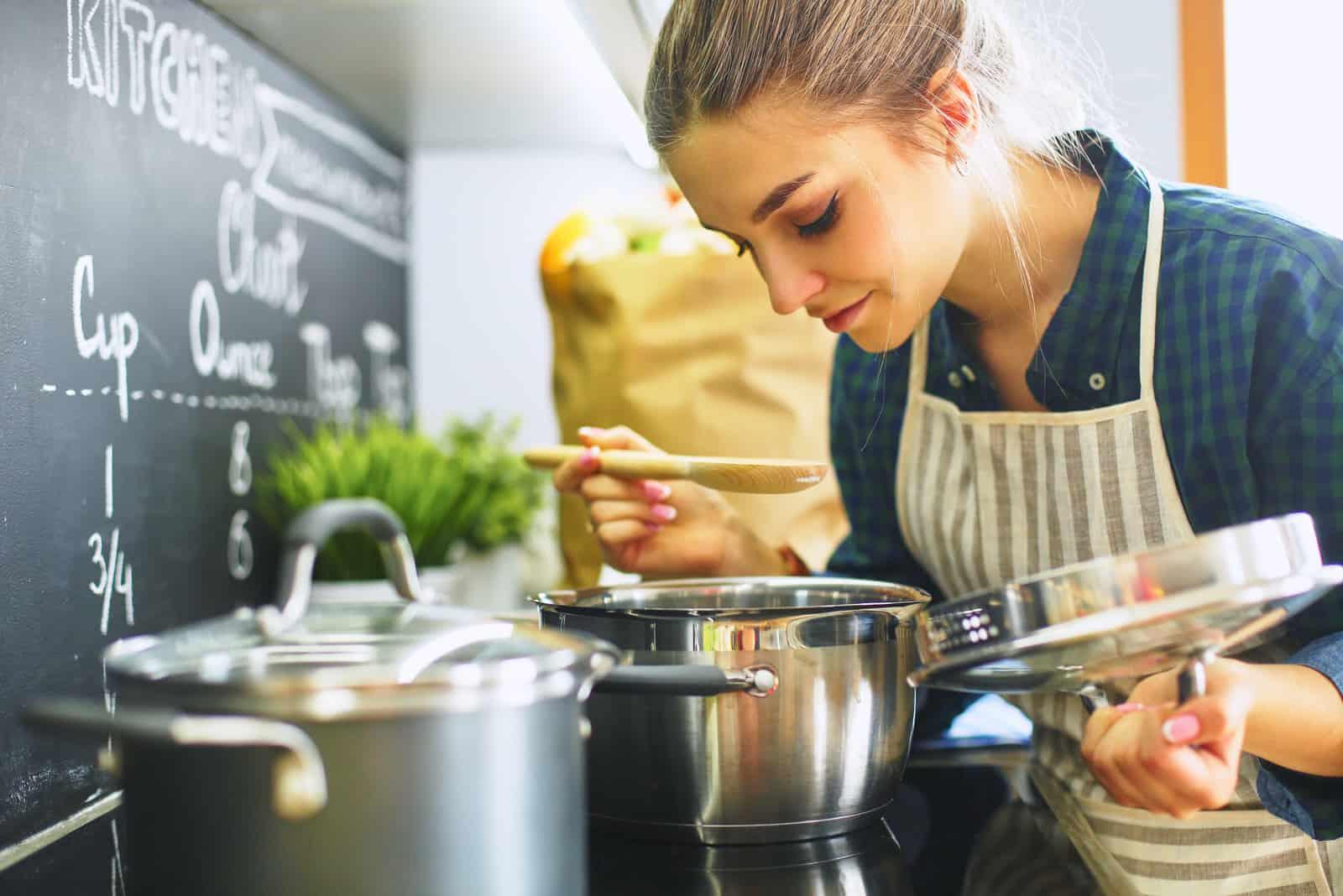 kvinna som lagar mat i sitt kök