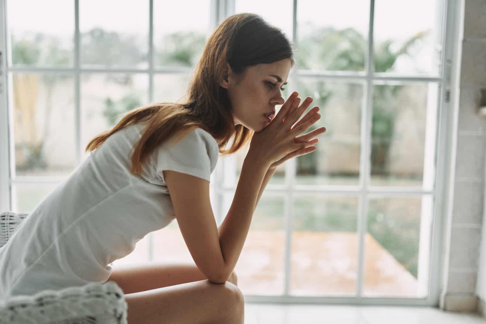 kvinna som sitter nära fönster