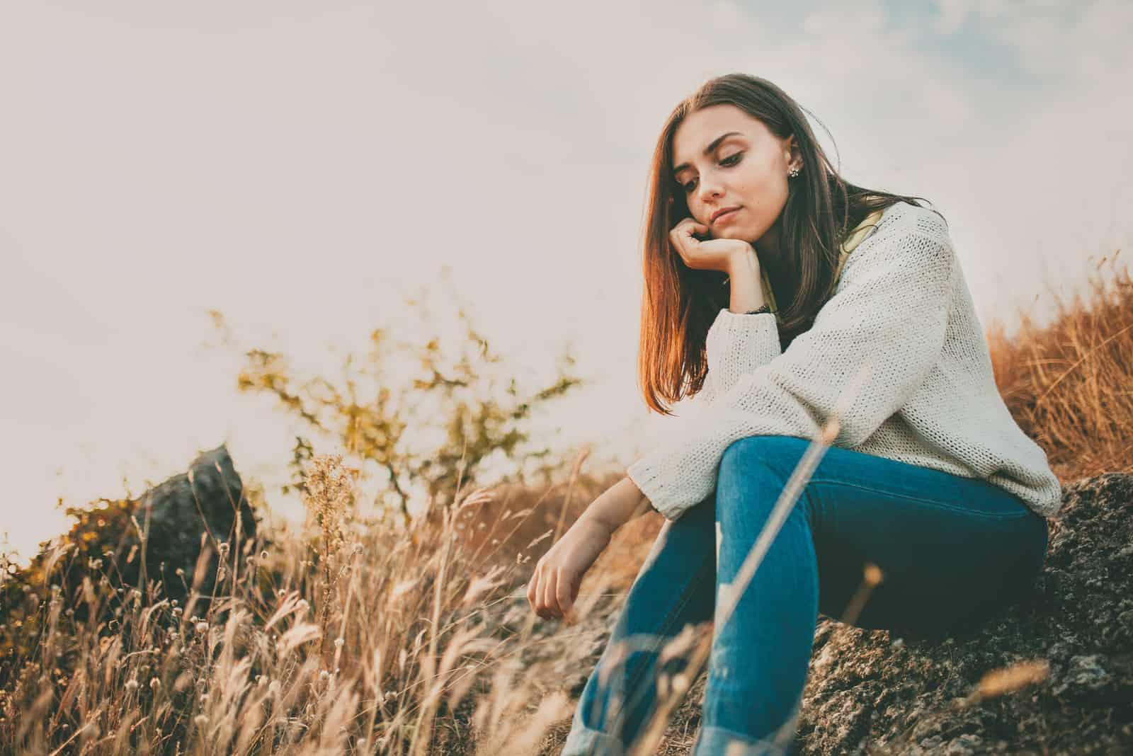 kvinna som sitter på gräset ensam