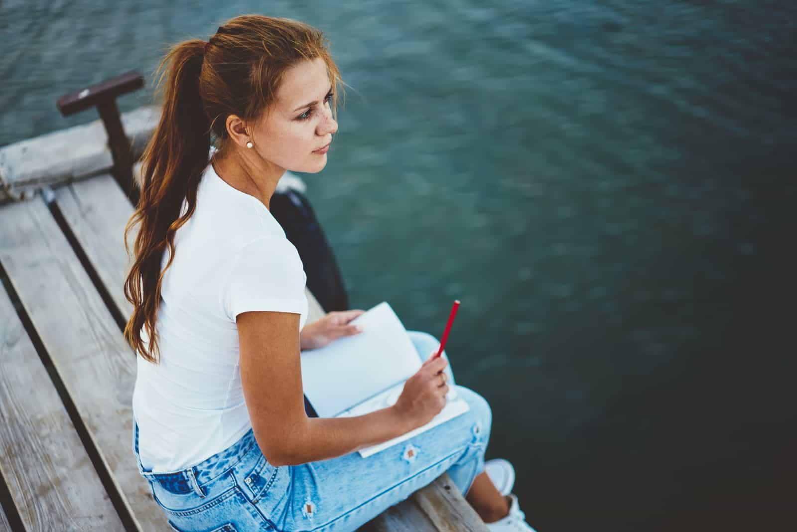 kvinnlig konstnär som vilar på pir nära floden