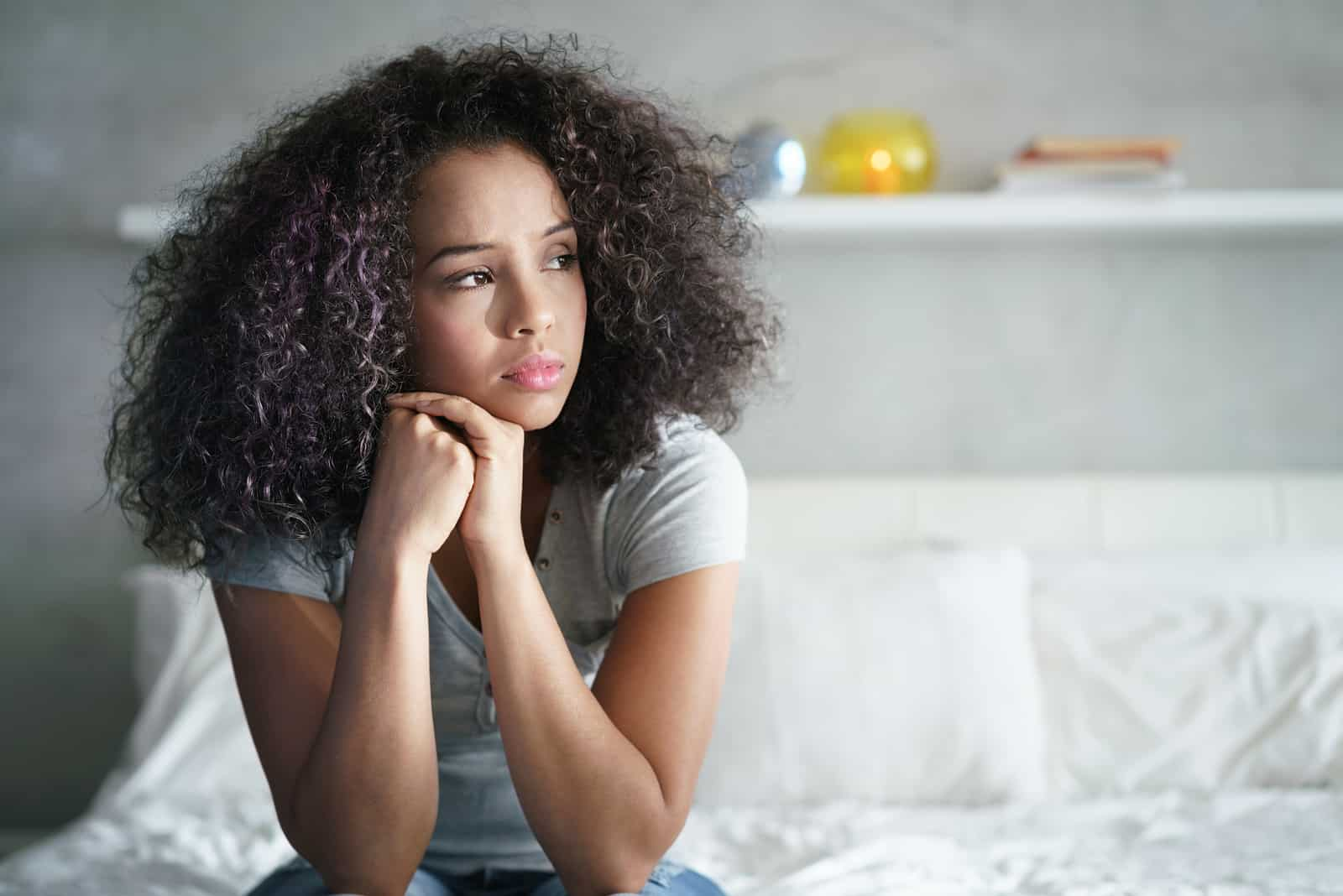ledsen ensam kvinna som sitter på sängen