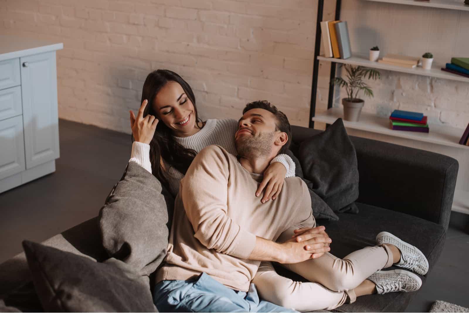 lyckliga par som kopplar av tillsammans på soffan hemma