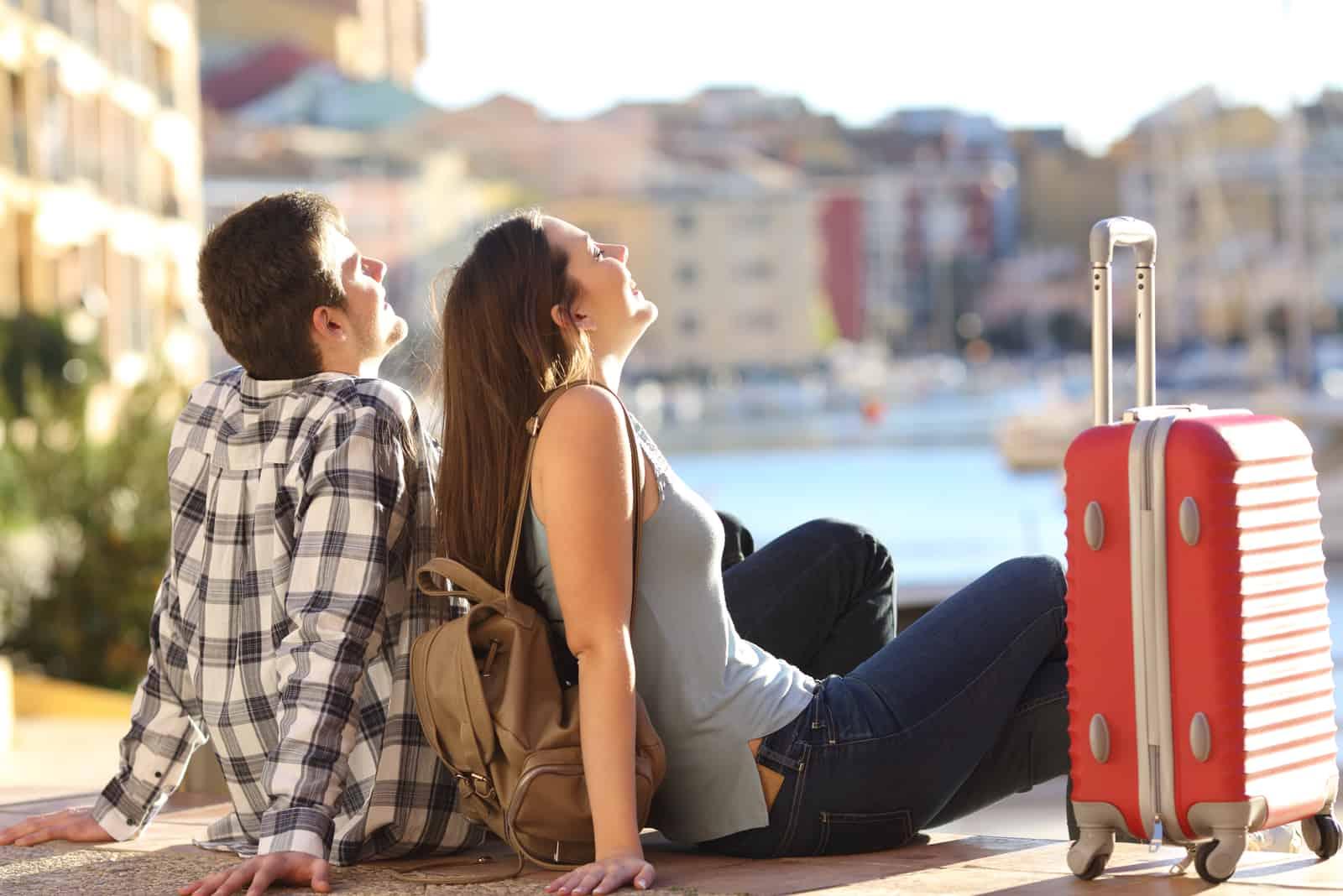 par av 2 turister med en resväska som sitter avkopplande