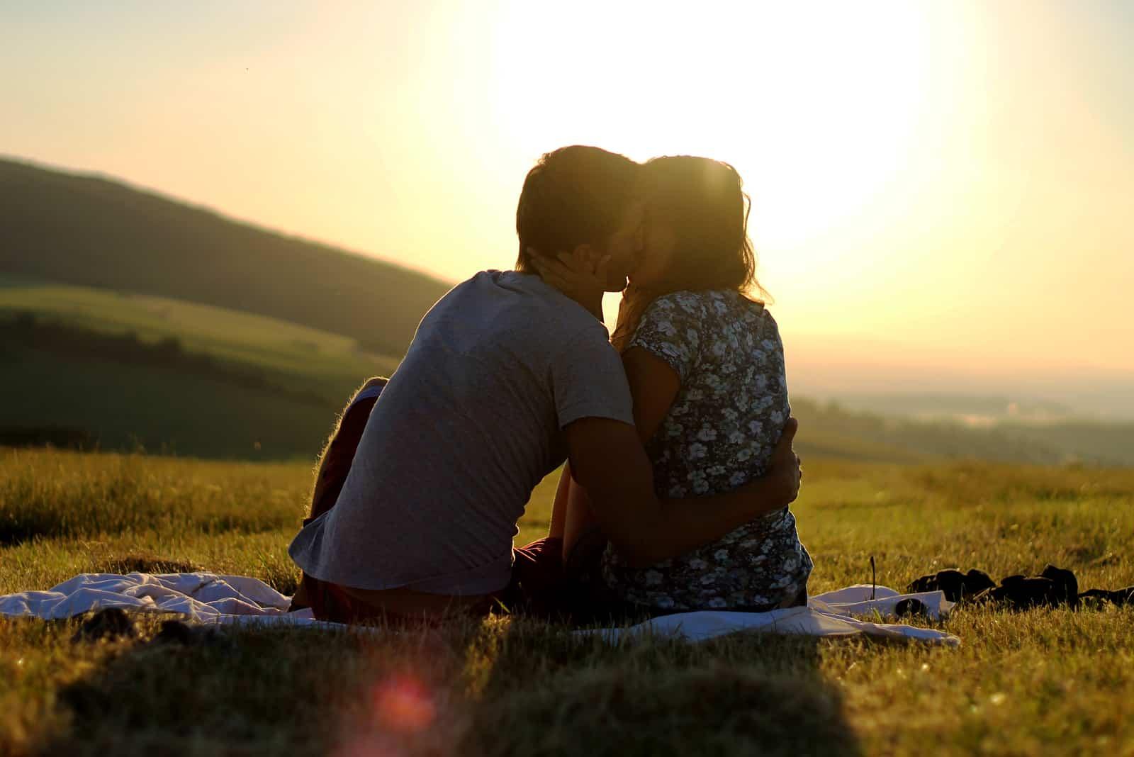 par sitter på gräs kyssar